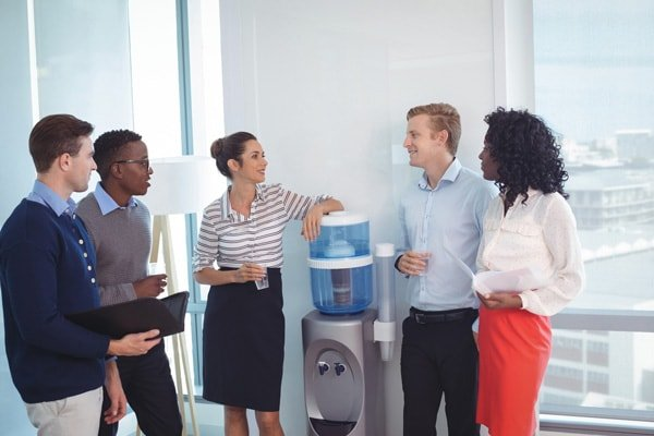 Office Water and Ice Solutions in Dallas, coworkers surrounding a water cooler