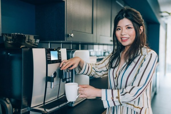 A woman using a cofeee dispenser to get fresh coffee, leading breakroom services management company